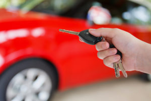 A hand activating a car key and remote with a car in the background